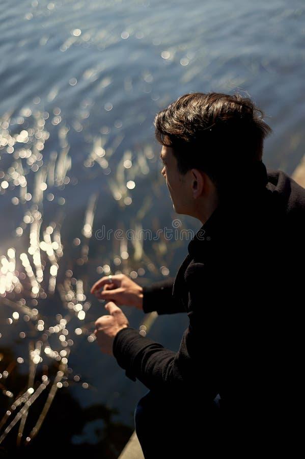 Młody wysoki mężczyzna w czarnym żakieta obsiadaniu wodą i spojrzeniach w odległość zdjęcie royalty free