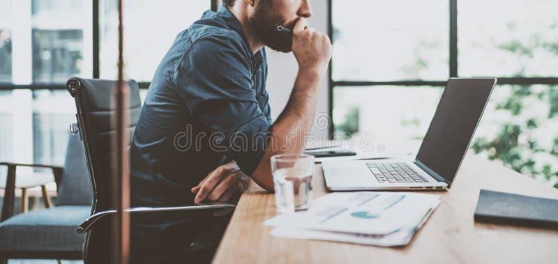 Młody zadumany coworker pracuje przy pogodnym miejsca pracy loft podczas gdy siedzący przy drewnianym stołem Mężczyzna analizuje  zdjęcie stock
