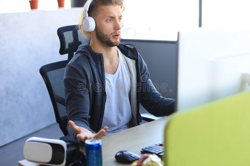 Młody, zdenerwowany grał w gry wideo online na komputerze i czuł się przygnębiony fotografia stock