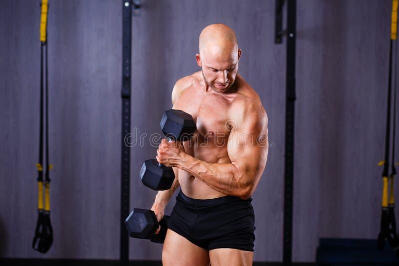 Młody zdrowy łysy rozdzierający mężczyzna trenuje z duma z dużymi mięśniami obraz stock