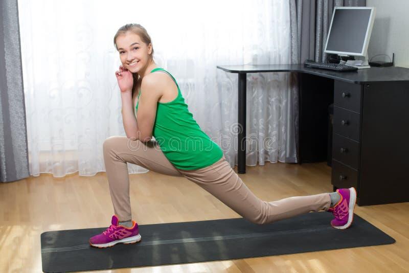 Młody zdrowy kobiety rozciąganie na joga matuje w domu obraz royalty free