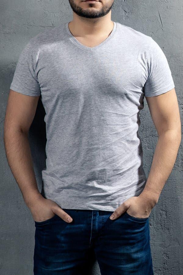 Młody zdrowy mężczyzna z popielatą koszulką na betonowym tle zdjęcia royalty free