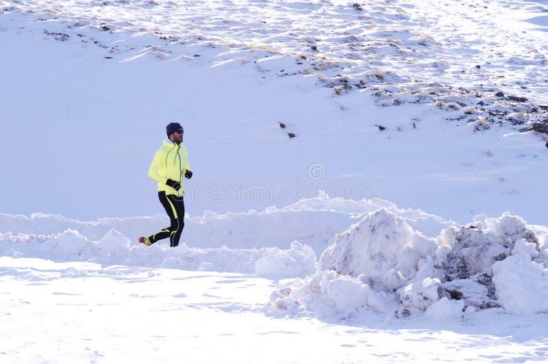 Młody zdrowy sporta mężczyzna bieg w śnieżnych górach w śladu biegacza ciężkim treningu w zimie zdjęcie stock