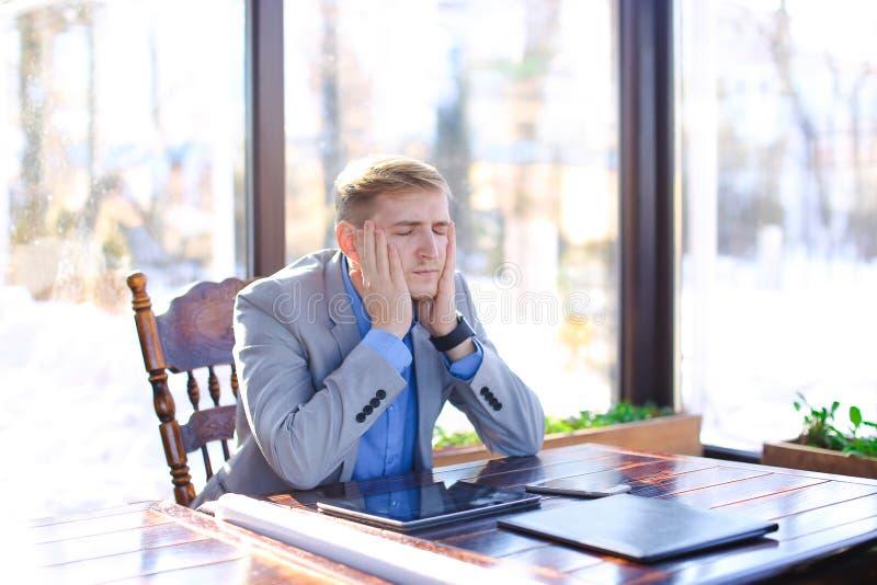 Młody zmęczony kierownik ma przerwę przy kawiarnią z rolka papierem, pastylka fotografia stock