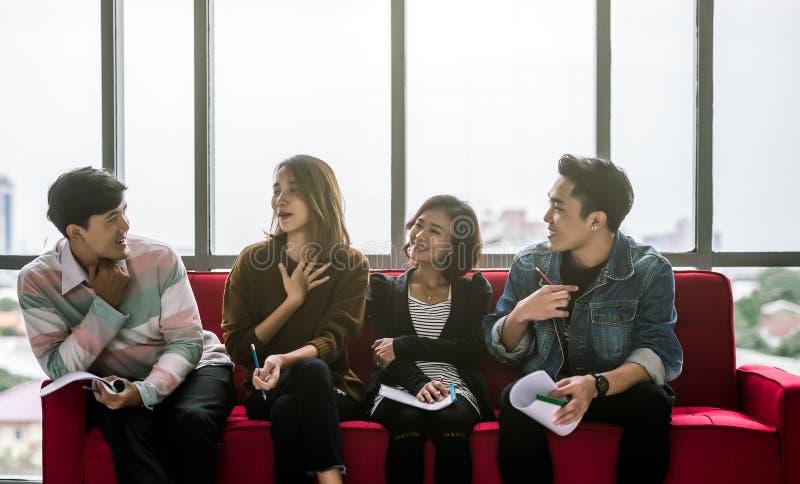 Młodych Azjatyckich przyjaciół grupowy opowiadać w biurze fotografia royalty free