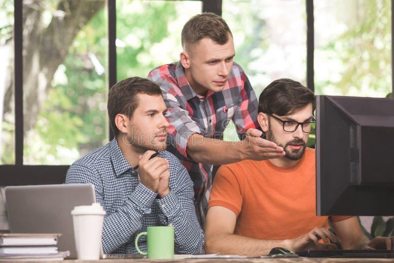Młodych człowieków programiści pracuje wpólnie w biurze obraz stock