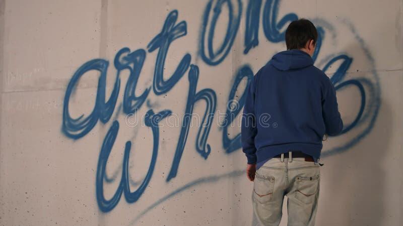 Młodych człowieków rysunkowi graffiti na ścianie z kiści puszką obraz royalty free
