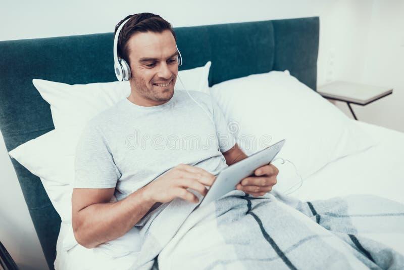 Młodych Człowieków Uses ochraniacz i Słucha muzyka w łóżku obrazy stock