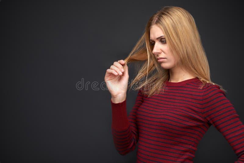 Młodych dziewczyn spojrzeń spęczenie przy kędziorami jej włosy i myśleć o dlaczego dawać one zdrowemu spojrzeniu i dostawać ono p fotografia royalty free