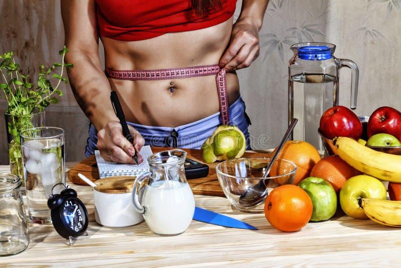 Młodych kobiet miary detoxification Młoda dziewczyna mierzy talię i używa właściwego odżywianie Detox napoje, składniki, dumbbell zdjęcia stock