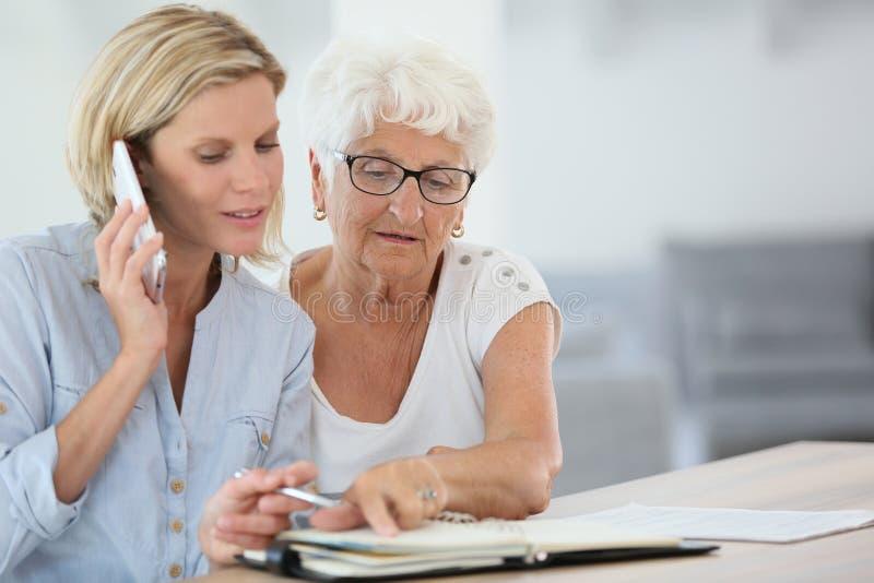 Młodych kobiet organizatorscy spotkania dla starszej kobiety obrazy stock