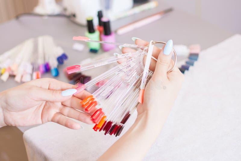 Młodych kobiet ręki wybiera gwoździa kolor Kobiety robić manikiur gwoździa koloru próbki i ręki fotografia stock