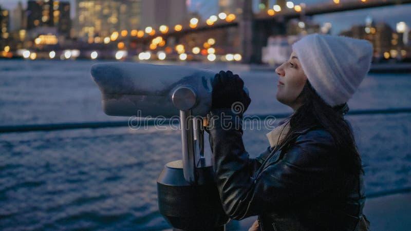 Młodych kobiet spojrzenia przez spyglass przy mostem brooklyńskim Nowy Jork obrazy stock