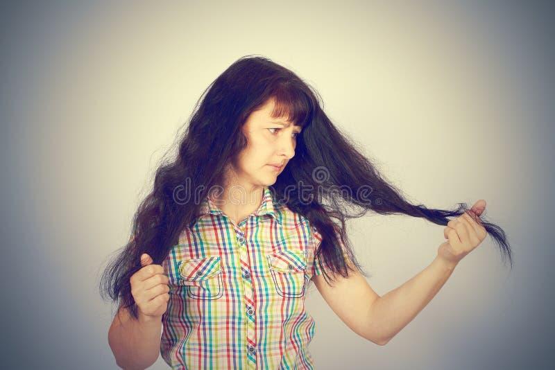 Młodych kobiet spojrzenia przy jej problemaycznym włosy fotografia royalty free