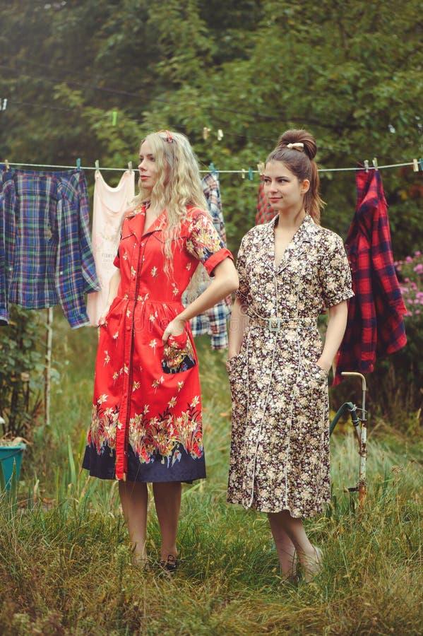 Młodych kobiet wieszać odziewa po myć w podwórzu w na wolnym powietrzu, żeńskim życiu i zabawie, obrazy royalty free