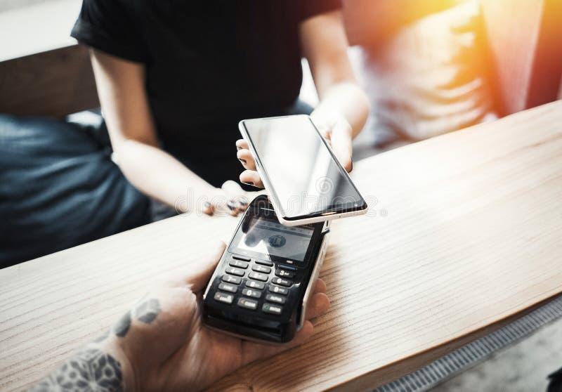 Młodych kobiet wynagrodzenia przez płatniczego terminal i telefonu komórkowego zdjęcia stock