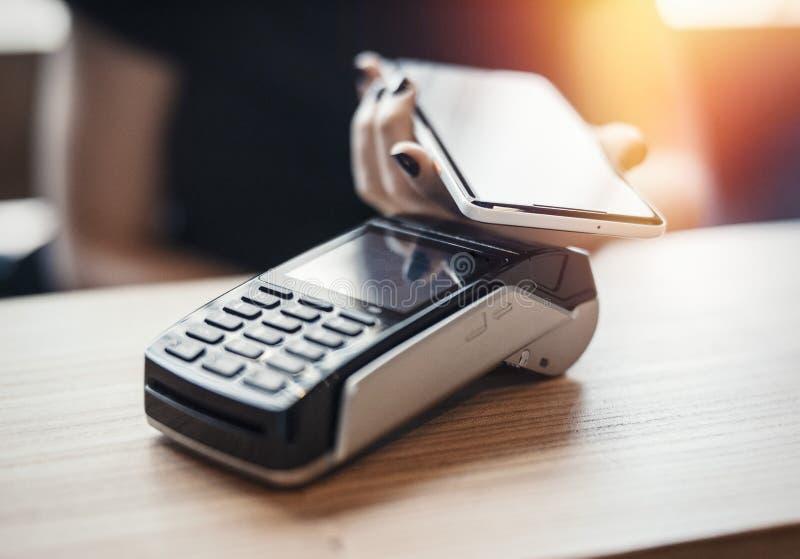 Młodych kobiet wynagrodzenia przez płatniczego terminal i telefonu komórkowego obrazy royalty free