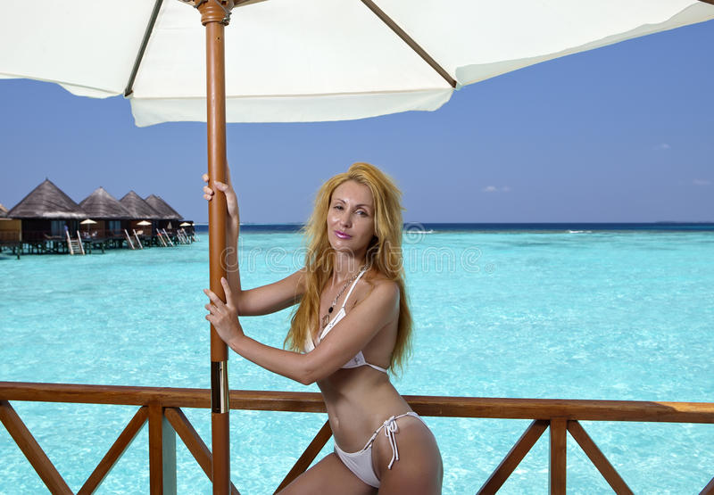 Młodzi ładni kobieta stojaki w kostiumu kąpielowym na platformie przy willą na wodzie, Maldives obraz royalty free