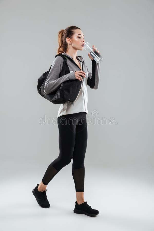 Młodzi ładni sprawności fizycznej kobiety przewożenia sporty zdosą i woda pitna fotografia stock