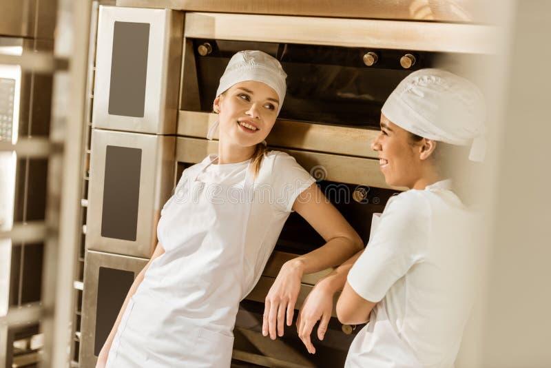 młodzi żeńscy piekarzi opiera na przemysłowym piekarniku przy pieczenie manufakturą obraz stock
