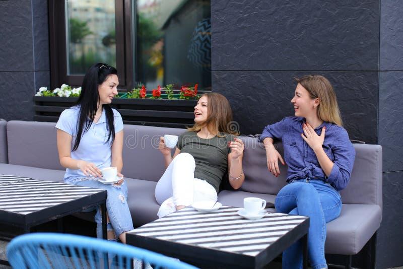 Młodzi żeńscy przyjaciele śmia się i opowiada przy kawiarnią, pije kawę obrazy royalty free