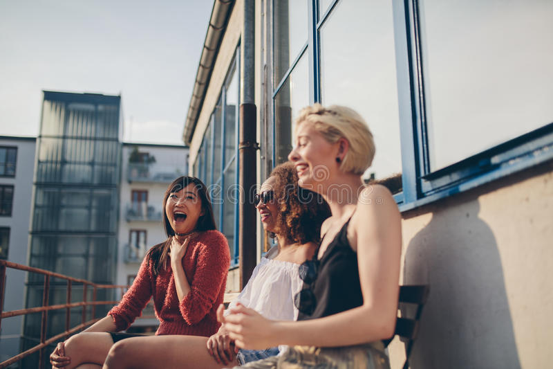 Młodzi żeńscy przyjaciele cieszy się w tarasie zdjęcia stock