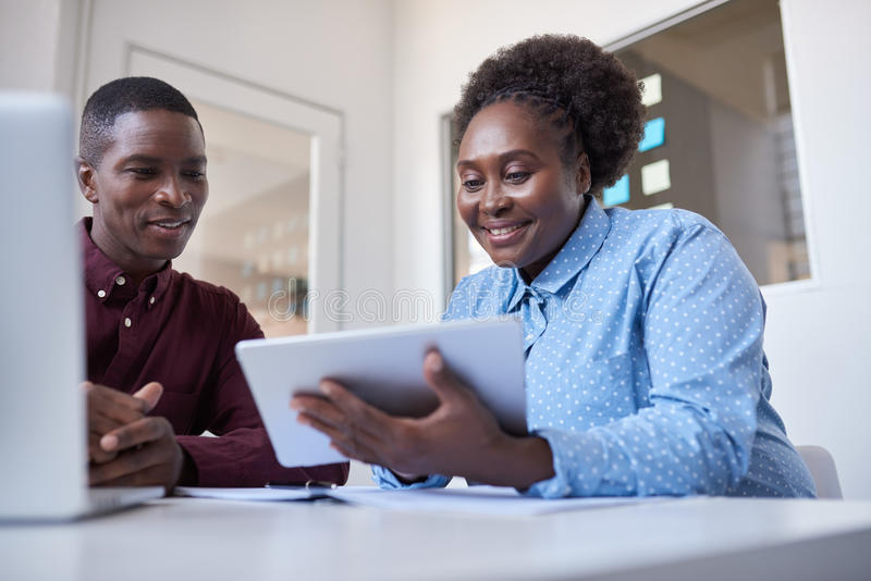 Młodzi Afrykańscy coworkers używa cyfrową pastylkę w biurze fotografia stock