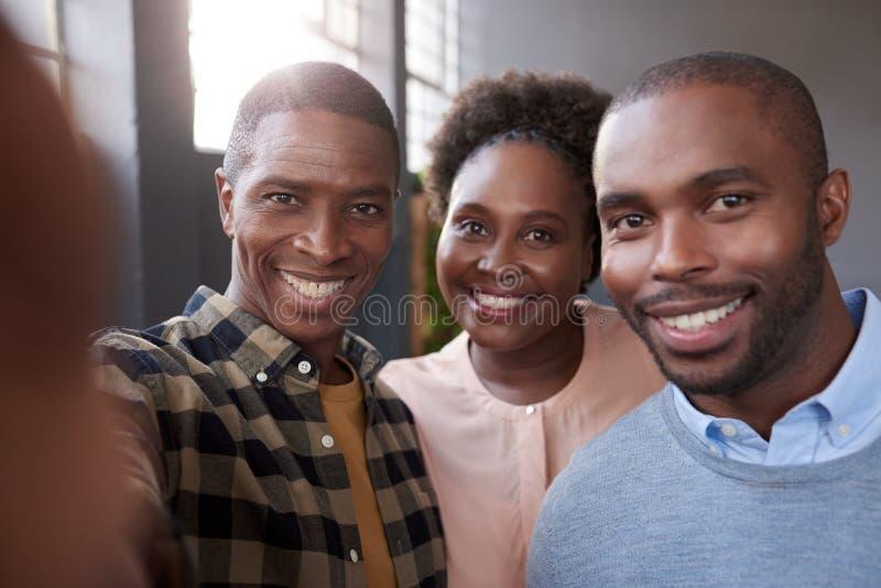 Młodzi Afrykańscy praca koledzy ono uśmiecha się wpólnie w biurze zdjęcie royalty free