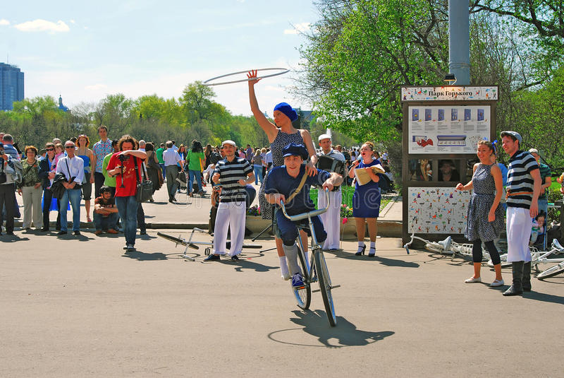 Młodzi aktorzy wykonuje w Gorky parku Wwoman i mężczyzna jedziemy bicykl fotografia royalty free