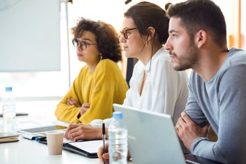 Młodzi atrakcyjni biznesmeni płaci uwagę w konferencji na coworking miejscu zdjęcia royalty free
