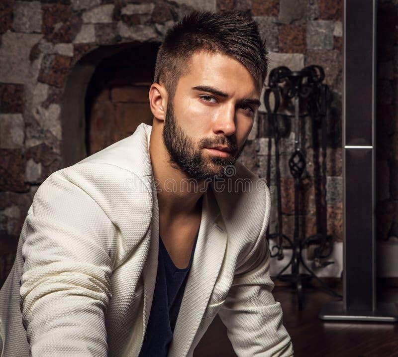 Młodzi atrakcyjni brodaci mężczyzna w białej kostium pozie w nowożytnym pokoju obraz royalty free
