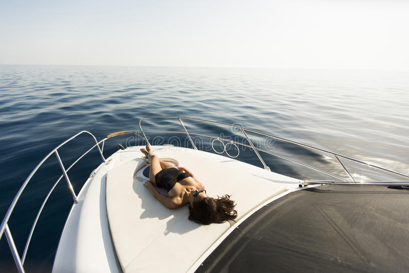 Młodzi atrakcyjni kobiet kłamstwa i sunbathing na łęku luksusowy jacht fotografia stock