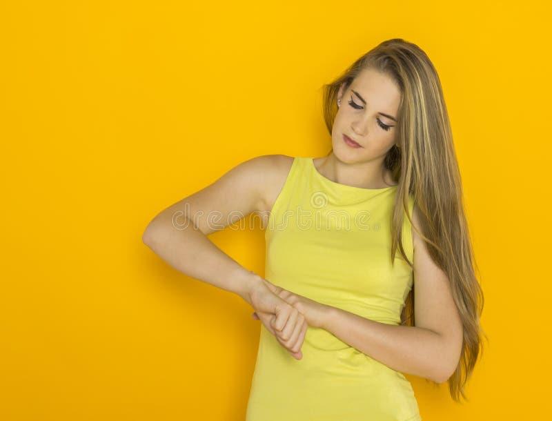 Młodzi atrakcyjni kobiet spojrzenia przy zegarem fotografia stock