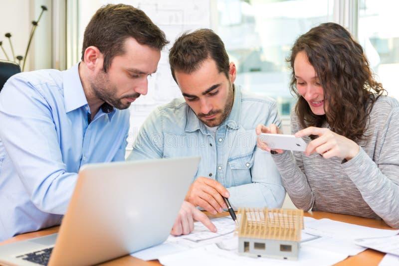 Młodzi atrakcyjni ludzie spotyka agenta nieruchomości przy biurem obraz stock