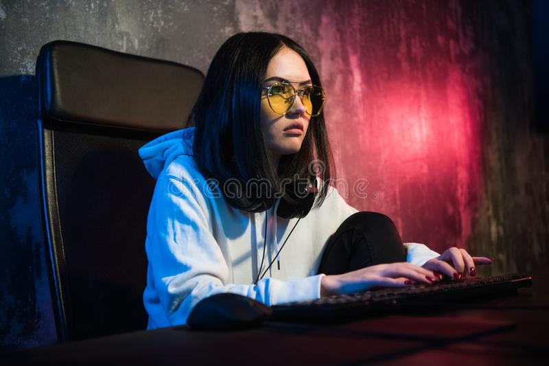 Młodzi atrakcyjni nastoletni kobiet eyeglasses na przyglądającym zmroku i niebezpieczny sieka system komputerowy na czarnym tle w zdjęcia royalty free