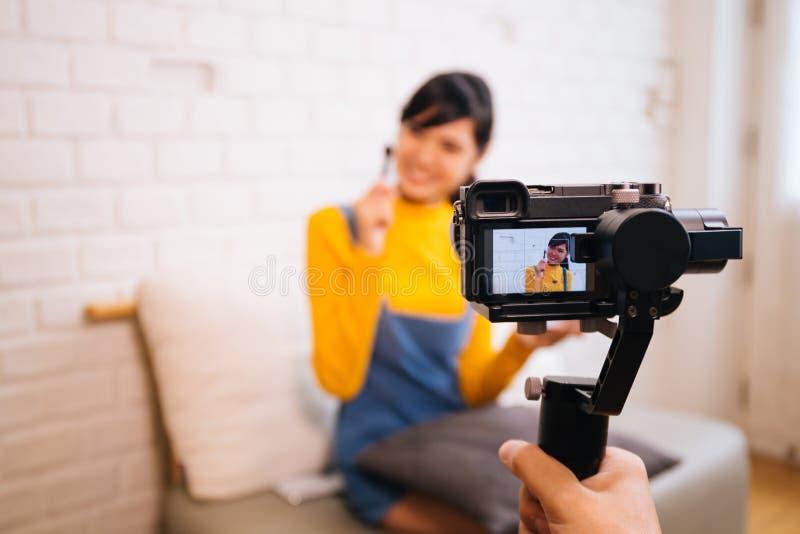 Młodzi Azjatyccy kobiety mienia kosmetyki szczotkują podczas gdy nagrywający wideo z fachową kamerą fotografia royalty free