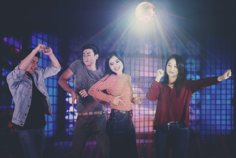 Młodzi Azjatyccy ludzie tanczy w klubie nocnym fotografia stock