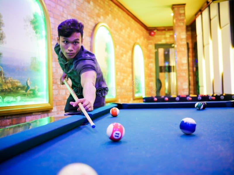 Młodzi Azjatyccy mężczyzna sztuki billiards w kolorowym klubie - Celować białą piłkę strzał zdjęcia royalty free