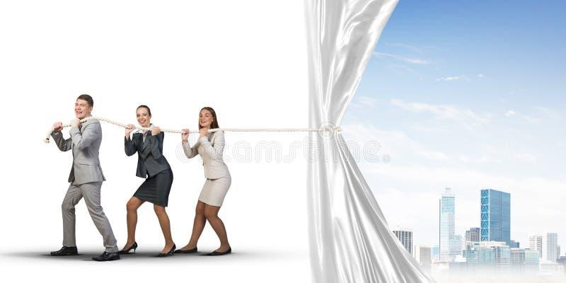 Młodzi biznesmeni pracuje w współpracy i ciągnie białego reklama sztandar zdjęcie stock