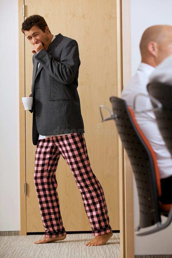 Młodzi biznesmeni walkin przez korytarz z pijamas dyszą zdjęcia royalty free