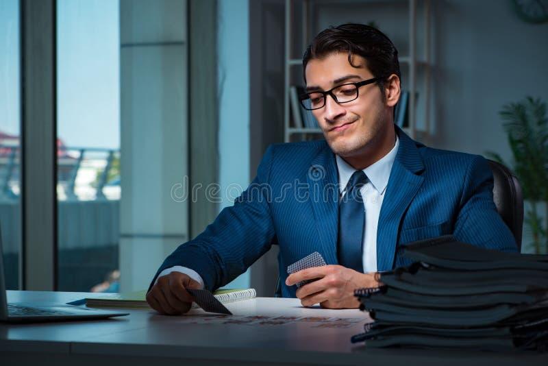 Młodzi biznesowi karta do gry póżno w biurze zdjęcie stock