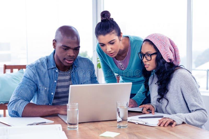 Młodzi biznesowi koledzy patrzeje laptop obrazy stock