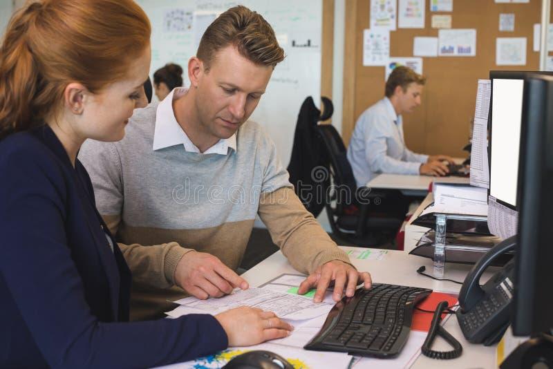 Młodzi biznesowi koledzy pracuje wpólnie przy biurem zdjęcie stock