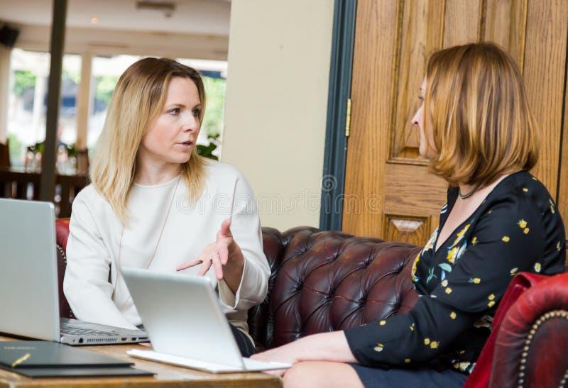 Młodzi bizneswomany ma rozmowę przy nieformalnym spotkaniem fotografia royalty free