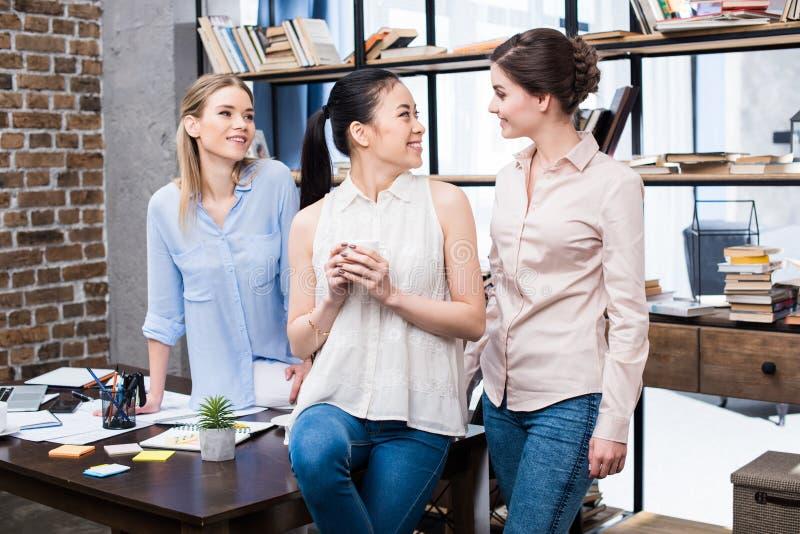 Młodzi bizneswomany opowiada przy miejscem pracy podczas gdy mieć kawową przerwę zdjęcie stock