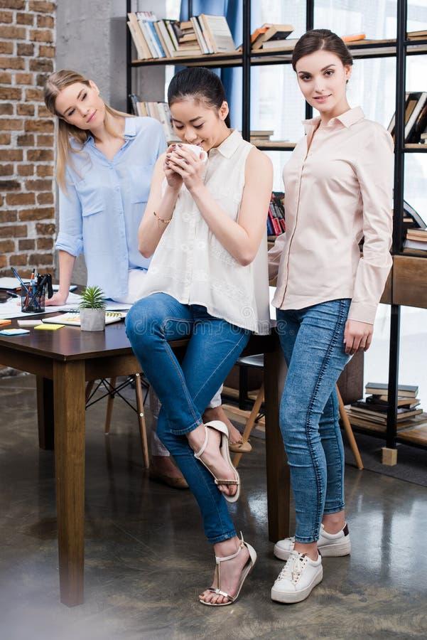 Młodzi bizneswomany opowiada przy miejscem pracy podczas gdy mieć kawową przerwę zdjęcia stock