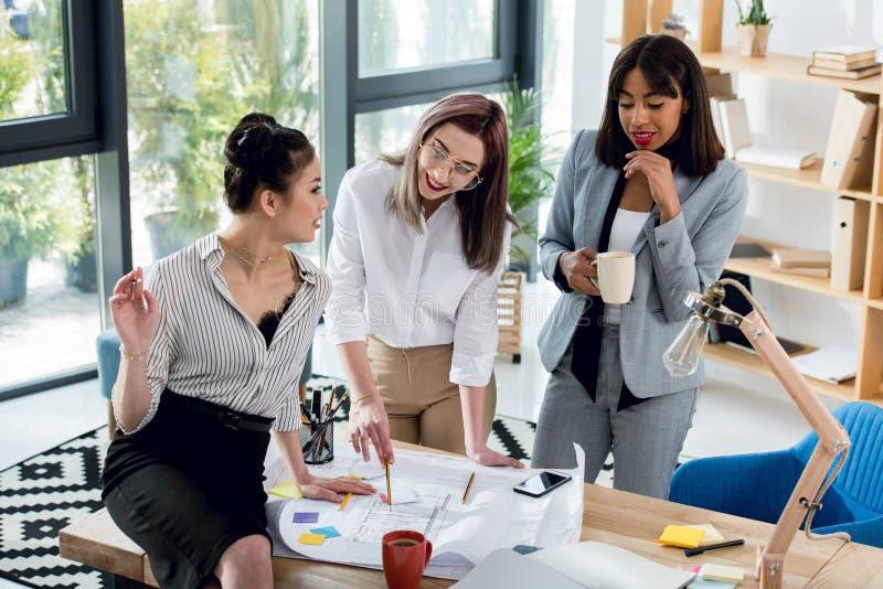 Młodzi bizneswomany pracuje z projektem i pije kawę w biurze obrazy royalty free