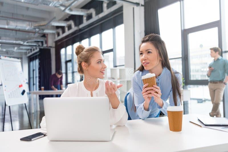 Młodzi bizneswomany używa laptop i opowiadający przy miejscem pracy fotografia stock