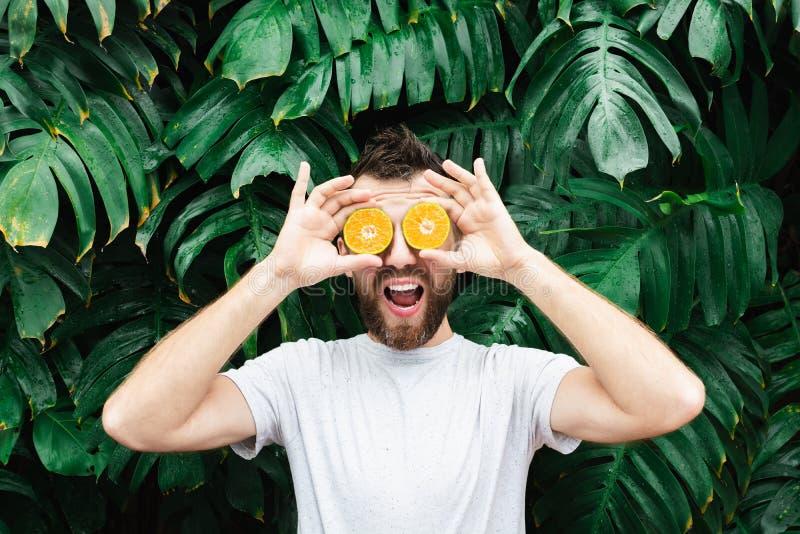 Młodzi brodaci mężczyzny mienia plasterki pomarańczowy tangerine przed jego one przyglądają się, śmiający się obrazy royalty free