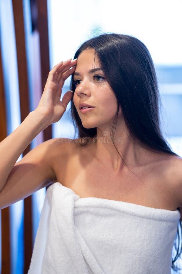 Młodzi brunetek spojrzenia w lustrze w białym ręczniku Dziewczyna przygotowywa brać skąpanie lub brać prysznić obraz royalty free